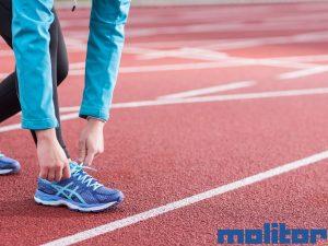 Frau bindet sich den Laufschuh auf der Laufbahn