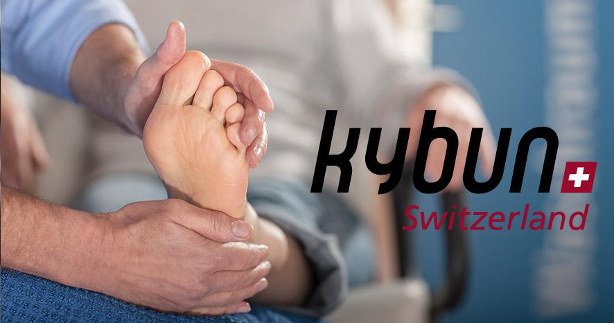 Mann hält Fuß in seinen Händen, rechts steht das kybun Switzerland Logo