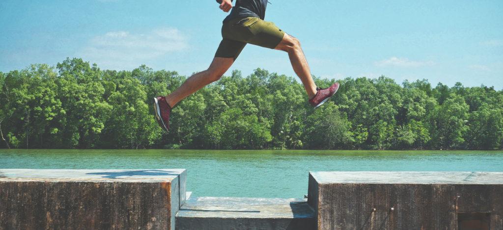 Mann mit roten Laufschuhen springt am See