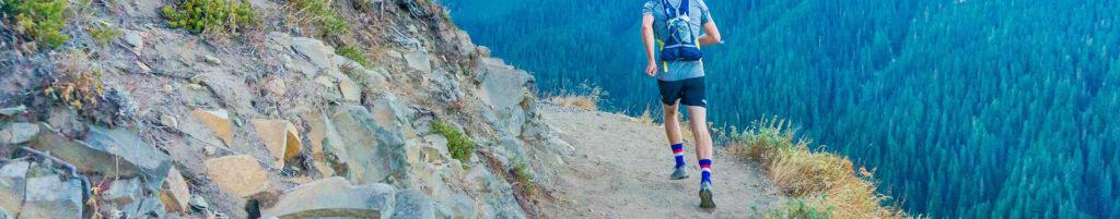 Mann joggt mit Rucksack draußen auf einem Berg
